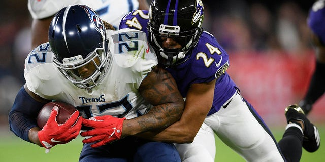Baltimore Ravens cornerback Marcus Peters (24) hits Tennessee Titans running back Derrick Henry (22) during an NFL divisional playoff football game, Saturday, Jan. 11, 2020, in Baltimore. (Associated Press)