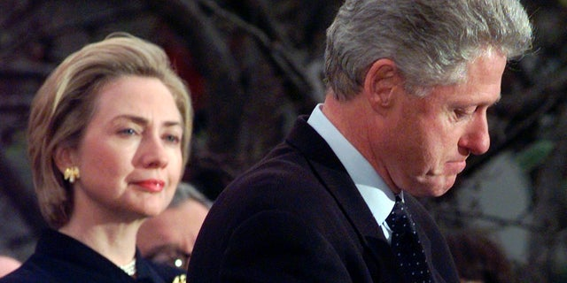 In this Dec. 19, 1998 file photo, first lady Hillary Rodham Clinton watches President Clinton pause as he thanks those Democratic members of the House of Representatives who voted against impeachment at the White House in Washington. (AP Photo/Susan Walsh, File)