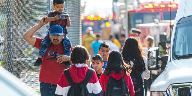 Children evacuate the Park Avenue Elementary school in Cudahy, Calif., on Tuesday. Fire officials say fuel apparently dumped by the aircraft returning to LAX fell onto the school's playground. (AP Photo/Damian Dovarganes)