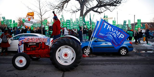 A Trump supporter rides by Democratic presidential candidate Sen. Amy Klobuchar, D-Minn., rally before a Democratic presidential primary debate Tuesday, Jan. 14, 2020, hosted by CNN and the Des Moines Register in Des Moines, Iowa. (AP Photo/Patrick Semansky)