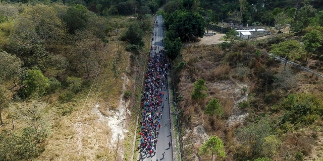 Migrants walk along a highway in hopes of reaching the distant United States, near Agua Caliente, Guatemala on Thursday near the border with Honduras. Hundreds of Honduran migrants started walking and hitching rides Wednesday from the city of San Pedro Sula, in a bid to form the kind of migrant caravan that reached the U.S. border in 2018. (AP Photo/Santiago Billy)