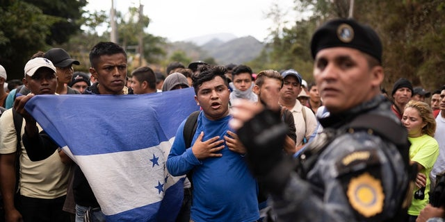 Honduran migrants walking in a group stop before Guatemalan police near Agua Caliente, Guatemala on Thursday on the border with Honduras. Hundreds of Honduran migrants started walking and hitching rides Wednesday from the city of San Pedro Sula, in a bid to form the kind of migrant caravan that reached the U.S. border in 2018. (AP Photo/Santiago Billy)