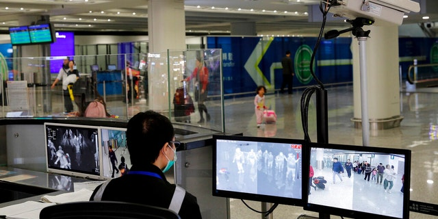 In this Jan. 4, 2020, file photo, a health surveillance officer monitors passengers arriving at the Hong Kong International airport in Hong Kong.  (AP Photo/Andy Wong, File)