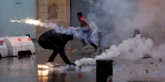 A protester throws back tear gas canister that was fired towards them by Lebanese riot police during an anti-government protest at a road leading to the parliament building in Beirut, Lebanon, Saturday, Jan. 18, 2020. Riot police fired tears gas and sprayed protesters with water cannons near parliament building to disperse thousands of people after riots broke out during a march against the ruling elite amid a severe economic crisis. (AP Photo/Hassan Ammar)