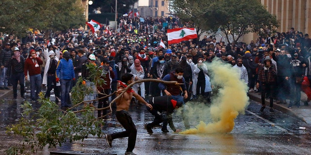 Anti-government demonstrators clash with riot police at a road leading to the parliament building in Beirut, Lebanon, Saturday, Jan. 18, 2020. Riot police fired tears gas and sprayed protesters with water cannons near parliament building to disperse thousands of people after riots broke out during a march against the ruling elite amid a severe economic crisis. (AP Photo/Bilal Hussein)