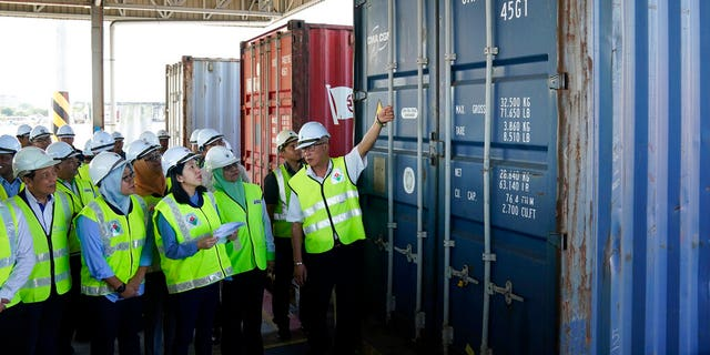 Malaysia's Environment Minister Yeo Bee Yin, third from left, inspects a container with plastic waste at a port in Butterworth, Malaysia, Monday, Jan. 20, 2020.