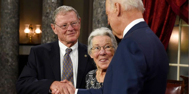 In this Jan. 6, 2015 file photo, Vice President Joe Biden shakes hands with Sen. James Inhofe, R-Okla., accompanied by Inhofe's wife Kay, center, after taking the Senate oath during a ceremonial re-enactment swearing-in ceremony in Washington. Inhofe's wife, Kay, suffered what he described as a mild stroke last week, causing him to miss the first day of impeachment trial proceedings, Oklahoma's senior U.S. senator said on Tuesday, Jan, 21, 2020. (AP Photo/Susan Walsh File)
