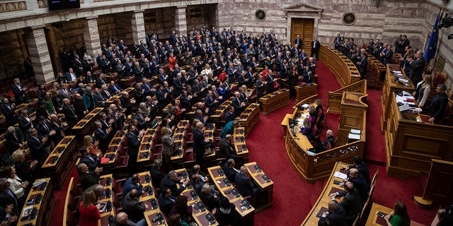 Greek lawmakers applaud during a parliamentary session to vote for the new Greek President, in Athens, on Wednesday, Jan. 22, 2019. High court judge Katerina Sakellaropoulou has been elected at Greece's first female president with an overwhelming majority in a parliamentary vote. (AP Photo/Petros Giannakouris)