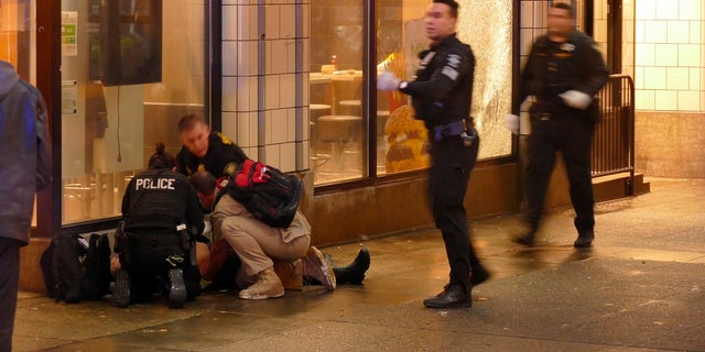 Officers attend to one of several shooting victims, outside of a McDonald's on Seattle's Third Avenue. The window of the restaurant behind them was shattered after a gunman opened fire in the heavily trafficked downtown area. (David Silver via AP)