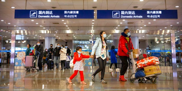 Travelers in face masks walk past a display board showing a canceled flight from Wuhan at Beijing Capital International Airport in Beijing.