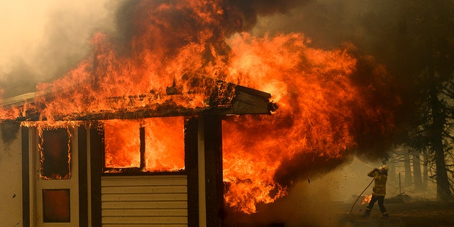 Jan. 23, 2020: A firefighter battles the Morton Fire as it consumes a home near Bundanoon, New South Wales, Australia. (AP Photo/Noah Berger)