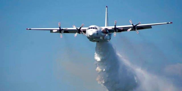 """In this undated photo released from the Rural Fire Service, a C-130 Hercules plane called """"Thor"""" drops water during a flight in Australia. Officials in Australia on Thursday, Jan. 23, 2020, searched for a water tanker plane feared to have crashed while fighting wildfires. (RFS via AP)"""