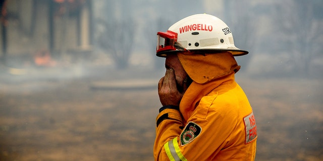 A firefighter covers his face while battling the Morton Fire near Bundanoon, New South Wales, Australia, on Thursday, Jan. 23, 2020.