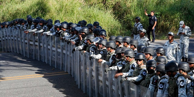 Mexican National Guardsmen block the passage of migrants on the highway leading to Tapachula, Mexico on Thursday. Hundreds of Central American migrants crossed the Suchiate River into Mexico from Guatemala Thursday after a days-long standoff with security forces. (AP Photo/Marco Ugarte)