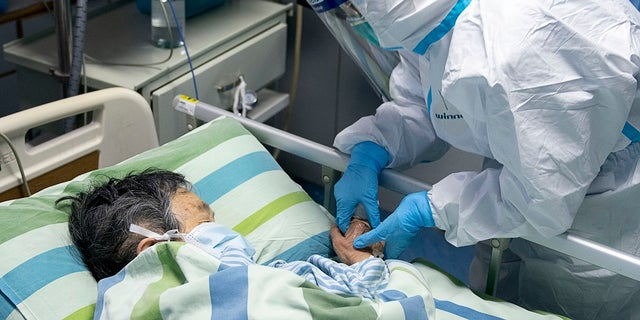 A medical worker attends to a patient in the intensive care unit at Zhongnan Hospital of Wuhan University in Wuhan in central China's Hubei Province. C(Xiong Qi/Xinhua via AP)