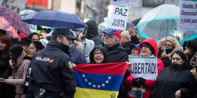 A woman holds a Venezuelan flag as others pack the Puerta del Sol square waiting for Juan Guaido during his visit to Madrid, Spain, Saturday, Jan. 25, 2020. Juan Guaido, the man who one year ago launched a bid to oust Venezuelan President Nicolas Maduro, arrived Saturday in Spain, where a thriving community of Venezuelans and a storm among Spanish political parties awaited him. Banners read 'Peace and6Freedom' (AP Photo/Paul White)