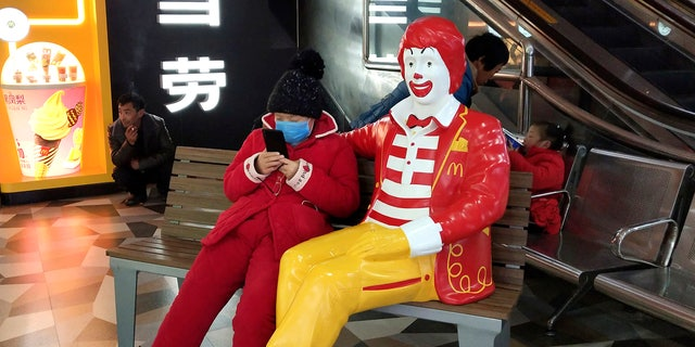 A woman wears a face mask and she uses her smartphone as she sits next to a statue of Ronald McDonald at a McDonald's restaurant in Suzhou in eastern China's Jiangsu Province on Jan. 26. (Chinatopix via AP)