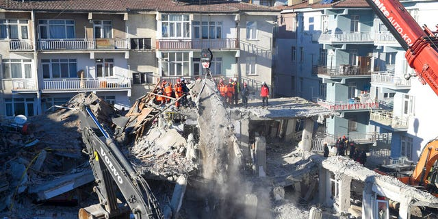 Rescue workers continue to look for people trapped under debris following a strong earthquake that destroyed several buildings on Friday, in Elazig, eastern Turkey, Sunday, Jan. 26, 2020.