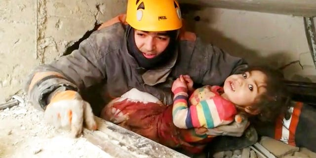 In this image taken from video made available by Ankara Municipality Fire Department shows a rescuer pulling out a girl from the rubble of a collapsed building, in Elazig, Turkey, Saturday Jan. 25, 2020.