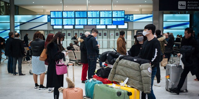 Travelers from Beijing, wearing masks, arrive at Charles de Gaulle airport, north of Paris, early Monday, Jan. 27, 2020. (AP Photo/Kamil Zihnioglu)