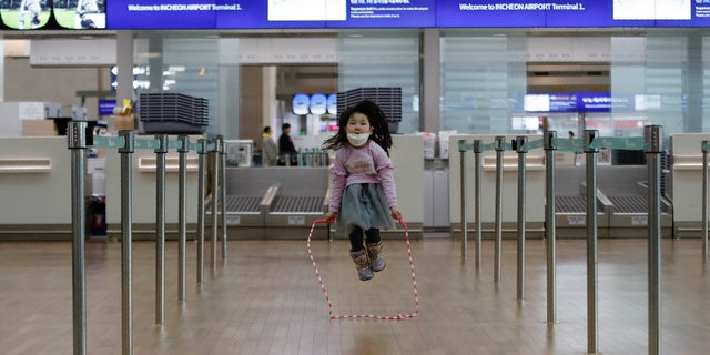 A girl wearing a mask skips rope at Incheon International Airport in Incheon, South Korea, Monday, Jan. 27, 2020. (AP Photo/Ahn Young-joon)