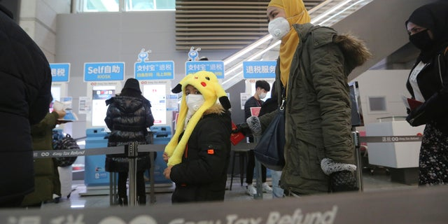 Passengers wear masks in a departure lobby at Incheon International Airport in Incheon, South Korea, Monday, Jan. 27, 2020. (AP Photo/Ahn Young-joon)
