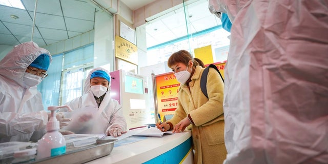Medical workers in protective gear talk with a woman suspected of being ill with a coronavirus at a community health station in Wuhan in central China's Hubei Province on Monday. The State Department is urging Americans to reconsider travel to China. (Chinatopix via AP)
