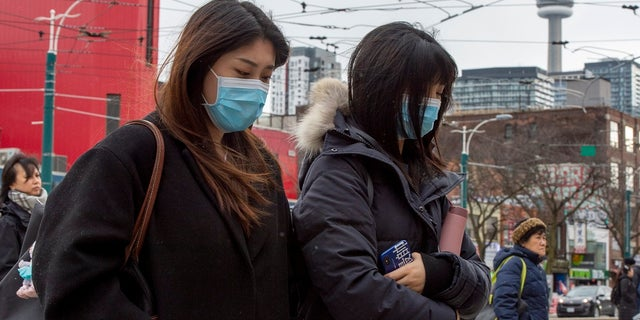 Pedestrians wear protective masks as they walk in Toronto on Monday. Canada's first presumptive case of the novel coronavirus has been officially confirmed, Ontario health officials said Monday as they announced the patient's wife has also contracted the illness. Surgical-style masks at U.S. pharmacies have reportedly begun selling out in several cities amid fears of the virus. (Frank Gunn/The Canadian Press via AP)