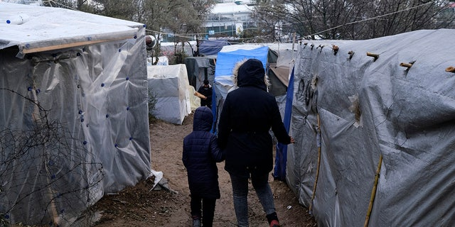 Migrants walk between makeshift tents outside the perimeter of the overcrowded Moria refugee camp after a rainfall on the northeastern Aegean island of Lesbos, Greece, Tuesday, Jan.28, 2020.