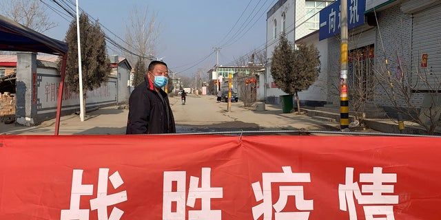 "A man wearing a face mask stands near a banner reading ""defeat the epidemic"" stretched across the entrance to Donggouhe village in northern China's Hebei Province. (AP Photo)"