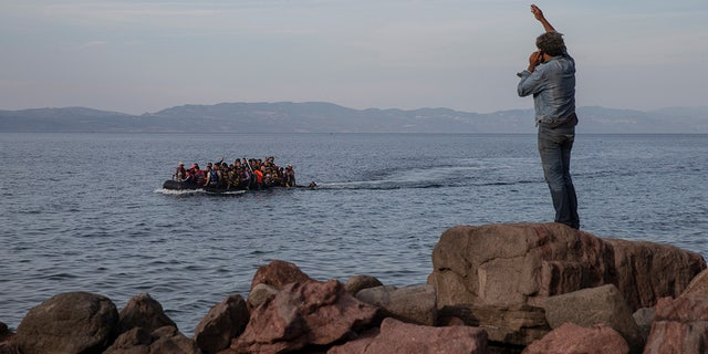 In this Wednesday, Sept. 9, 2015 photo refugees and migrants aboard an overcrowded dinghy as they cross the Aegean Sea, from Turkey, that is seen in the background, to the coast of Lesbos island, Greece. (AP Photo/Petros Giannakouris)