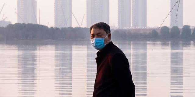 A man wears a face mask as he stands along the waterfront in Wuhan in central China's Hubei Province, Thursday, Jan. 30, 2020.