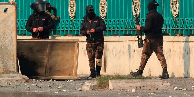 Security forces carry slingshots and a pellet air rifle during clashes with anti-government protesters in downtown Baghdad, Iraq on Thursday, Jan. The Iraqi military said it will resume operations with U.S.-led coalition forces after a three-week pause. (AP Photo/Hadi Mizban)