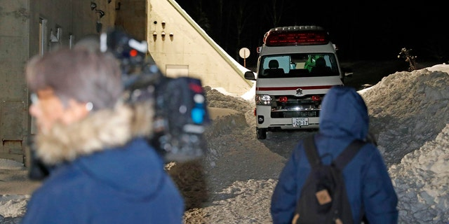 An ambulance waits as journalists, foreground, gather at the Tomamu ski resort in Shimukappu village, central Hokkaido, northern Japan, Thursday night, Jan. 30, 2020. An avalanche at the ski resort on Thursday hit a group of eight foreign skiers. (Yohei Fukai/Kyodo News via AP)