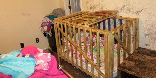 A wooden crib-shaped cage at the home appeared to have a slatted lid that opened and closed.