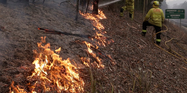 Firefighters manage a controlled burn to help contain a larger fire near Falls Creek, Australia, Sunday, Jan. 5, 2020.