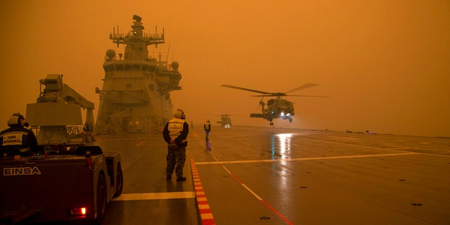In this photo provided by the Australian Department of Defense, a Royal Australian Navy Seahawk Helicopter departs from HMAS Adelaide while at sea off Australia's east coast, Sunday, Jan. 5, 2020, during operations to assist in battling wildfires.