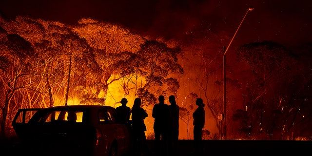 Residents look on as flames burn through bush on January 04, 2020 in Lake Tabourie, Australia. A state of emergency has been declared across NSW with dangerous fire conditions forecast for Saturday, as more than 140 bushfires continue to burn. There have been eight confirmed deaths in NSW since Monday 30 December. 1365 homes have been lost, while 3.6 million hectares have been burnt this fire season.