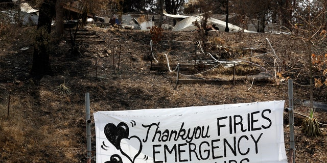 "A sign is displayed beside a burned-out house near Mogo, Australia, Thursday, Jan. 9, 2020, thanking ""firies"" a colloquial term for firefighters."