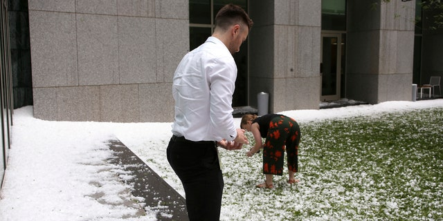 A man and woman collect golfball-sized hail on the grounds of Parliament House in Canberra, Australia, after a storm battered the Australian capital, Monday, Jan. 20, 2020.