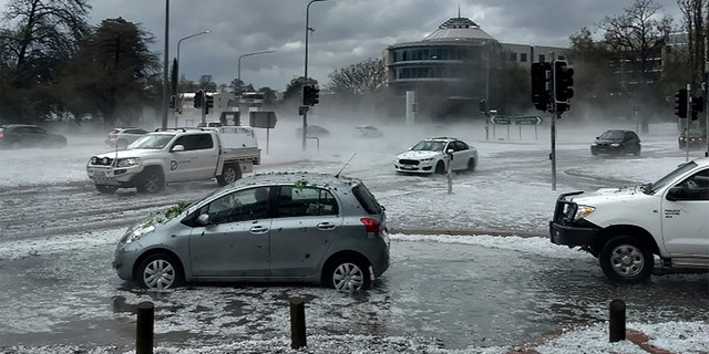 Hail covers vehicles in an intersection Jan. 20, in Canberra, Australia.