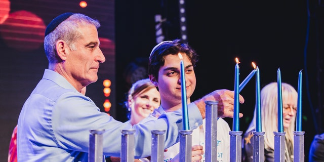 Birthright Israel CEO Gidi Mark lights the Hannukah menorah with participants at the 20th anniversary Hannukah kick-off event in Israel.