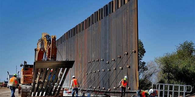 In this Sept. 10, 2019 photo, government contractors erect a section of Pentagon-funded border wall along the Colorado River in Yuma, Ariz. (AP Photo/Matt York)