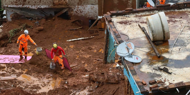 Firefighters search for victims near houses destroyed by a landslide after heavy rains in Barreiro, Minas Gerias state, Brazil, Saturday, Jan.25, 2020.