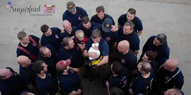 Brett Grace's grandfather, also a firefighter, holds her at a recent photo shoot with her father's fellow firefighters.