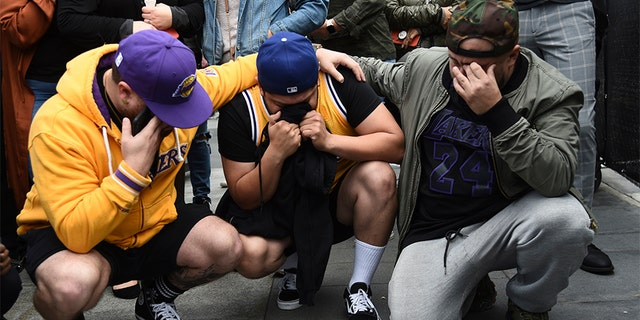 Los Angeles Laker fans Alex Fultz, from left, Eddy Rivas and Rene Alfaro mourn retired NBA star Kobe Bryant outside of the Staples Center prior to the 62nd annual Grammy Awards on Sunday, Jan. 26, 2020, in Los Angeles. Bryant died Sunday in a helicopter crash near Calabasas, Calif. He was 41. (AP Photo/Chris Pizzello)