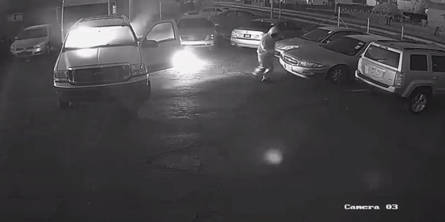 A man can be seen setting vehicles on fire in the parking lot of a business earlier this month in Phoenix.