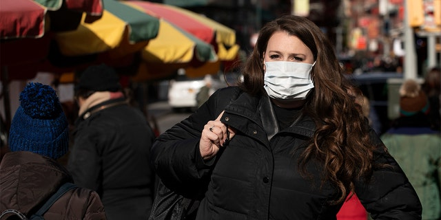 A woman, who declined to give her name, wears a mask, Thursday, Jan. 30, 2020 in New York City. She works for a pharmaceutical company and said she wears the mask out of concern for the coronavirus. (Associated Press)