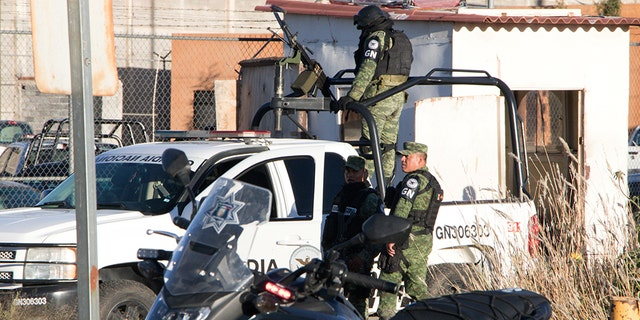 Members of the Mexican National Guard stand atop a vehicle as they keep watch outside the Cieneguillas state prison after sixteen inmates were killed and five were wounded in a brawl.