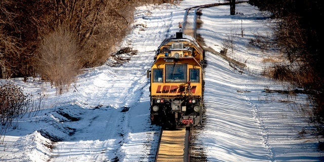 A train makes its way along a path where corn spilled from a train on a Canadian Pacific line in Crystal, Minn.
